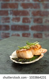 Scallops perfectly cooked on asparagus in a shell with garnish on slate with a brick wall backgrounds