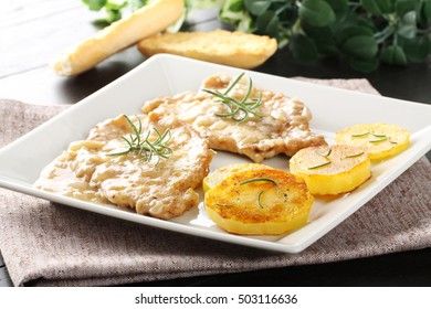 Scaloppina with rosemary with baked potatoes on complex background