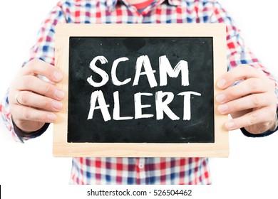 Scam alert / Man holding small blackboard.