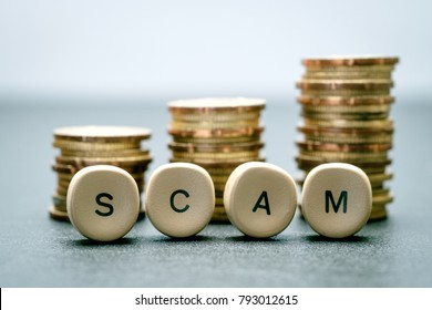 SCAM letter block and stack coins, business concept.