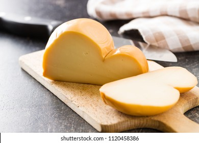 Scamorza, italian smoked cheese on cutting board.