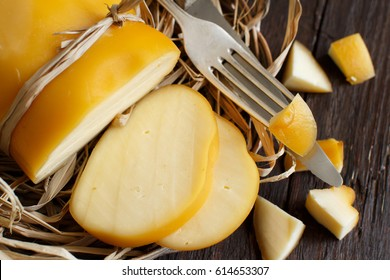 Scamorza, typical italian smoked cheese on wooden table