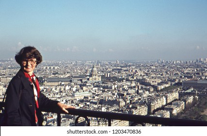 Scan of 1975 vintage analog image of a young woman in a blue coat and red scarf enjoying the view and posing on the Eiffel tower with Paris in the background.