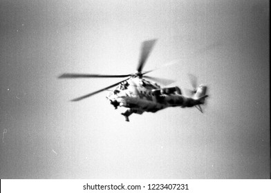 Scan of old dirty, grainy B&W 35mm negative from Cold War era with blurry image of soviet armoured assault helicopter.