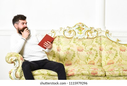 Scandalous bestseller concept. Guy reading book with amazement. Man with beard and mustache sits on baroque style sofa, holds book, white wall background. Macho on surprised face reading book.