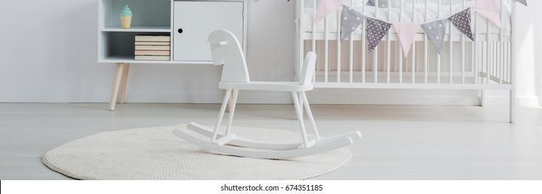 Scandi baby nursery with rocking horse and white crib