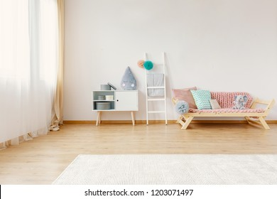 Scandi child room interior in real photo with carpet on the floor, window with drapes, cupboard with raindrop cushion and lounge with blanket and pompom