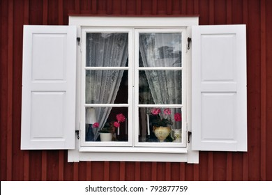 Scandinacian white window with flower pots and lace curtains