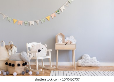 Scandinavian child room with grey wall, natural basket, teddy bear on children's chair and design toys. Cute modern interior with colorful cotton flags and wooden shelf with accessories. Copy space.
