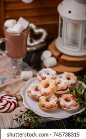 Scandinavian cookies filled with jam on a background with Christmas Decoration cocoa and candles.