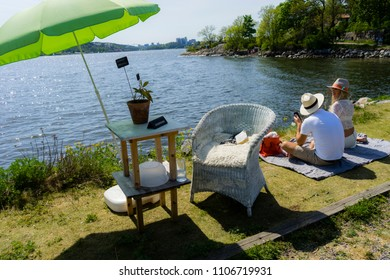 Scandinavian design/Idyllic scenery on the island of Fjäderholmarna where a couple all dresses up sits on a blanket next to a chair and a table with a plant and an umbrella. Stockholm, Sweden, May 19,