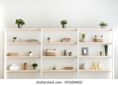 Scandinavian furniture with decorative elements in daylight. Gray wall and shelf with potted plants and accessories in modern living room, office or bedroom interior, flat lay, copy space, indoor
