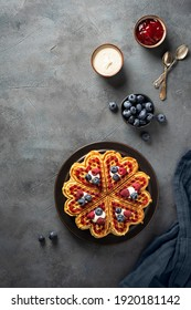 Scandinavian heartsweet waffles (heart shaped) with jam, sour cream and blueberries.  Place for text.