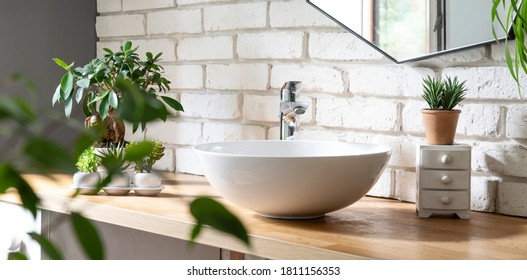 Scandinavian interior of bathroom with stylish washbasin, white brick wall, mirror and green leaves of plants. Bath and hygiene in spa. Panoramic.