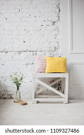 scandinavian interior. brick wall in white room. comfortable room. glass with plant on the floor. yellow pillow