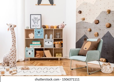 Scandinavian interior design of playroom with modern climbing wall for kids, design furnitures, mint armchair, soft toys, teddy bear and cute children's accessories. Mock up poster frame. Template.