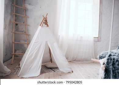 Scandinavian interior in white and gray. Children's tent of white color. Very bright and spacious room