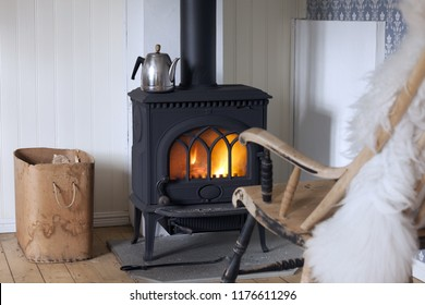 Scandinavian interior: wood burning stove, box of firewood and old restored rocking chair in living room corner. Metal coffeepot at stove. White sheep skin in rocking chair.