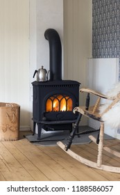 Scandinavian interior: wood burning stove, box of firewood and old restored rocking chair in living room corner. Metal coffeepot at stove. White sheep skin in rocking chair. Oiled wooden floor.