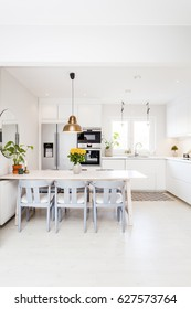 scandinavian kitchen interior with kitchen table and grey chairs