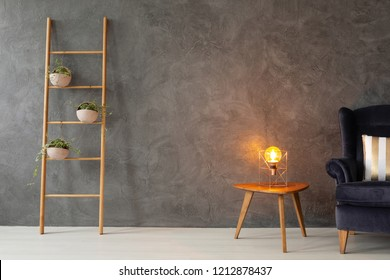 Scandinavian ladder with plants in stylish pots next to small coffee table with modern lamp and velvet armchair with pillow, real photo with copy space on concrete wall