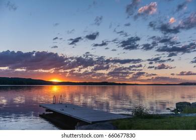 Scandinavian lake in the sunset with a long jetty. Midsummer sunset lake landscape. Scandinavian lake. Finland. Europe travel.