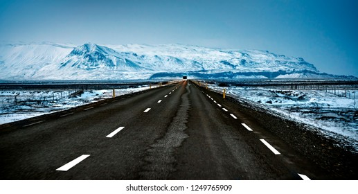 Scandinavian landscape, empty road in cold snowy country, far away view on the great mountains covered with snow, extreme car travel, road trip to Iceland