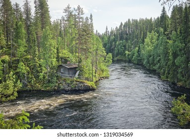Scandinavian landscape with an old fisherman's hut along the Oulankajoki river at the Oulanka National Park in Kuusamo, Finland. Scenic view of the northern nature and the flowing water in the stream.