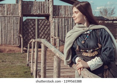 Scandinavian middle class woman in  historical suit posing over village. Her apparel based on archaeological sites on  Island of Gotland. Late 10th - 11th centuries.