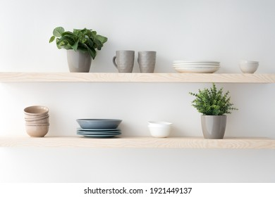 Scandinavian minimalist design in interior of apartment, flat for rent or sale and home blog. Modern plates and cups, kitchen utensils, potted plants on wooden shelves, on light wall, empty space