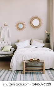 Scandinavian modern cozy interior. Wide bed with pillows, armchair and decorations in bedroom. Real photo