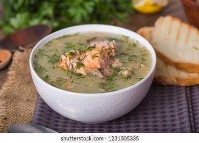 Scandinavian or Norwegian fish soup in bowl, cutting wooden board, spoon