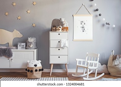 Scandinavian nursery room with mock up poster frame on the grey wall, white furniture, natural teddy bear and toys. Cute modern interior of playroom with white walls, baby accessories and toys.