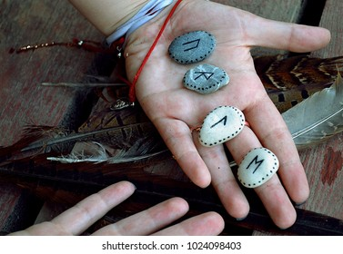 Scandinavian runes painted on sea stones in a female hand on a wooden floor with feathers. Close-up.
