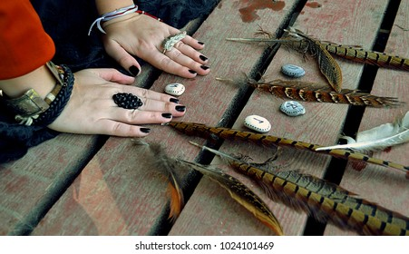 Scandinavian runes painted on sea stones in a woman's hand with rings and bracelets on a wooden floor with feathers. Close-up.