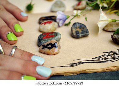 Scandinavian runes painted on sea pebbles: divination, runes - Dagaz, Raido, Hagalaz, Inguz on the book, women's hands with rings with a bouquet of wildflowers. Close-up.