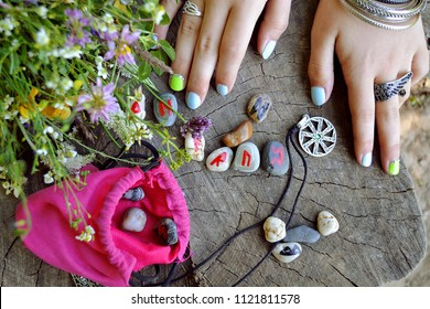 Scandinavian runes painted on sea pebbles a bag: divination, runes - Ansuz, Raido, Uruz, Pertho, Dagaz, beautiful women's hands with bracelets with a bouquet of wildflowers and a metal amulet.