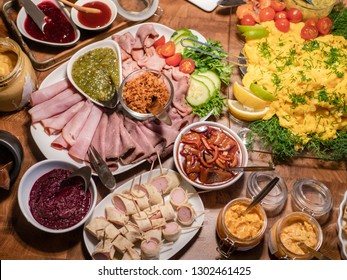 Scandinavian smorgasbord with an assortment of cold cuts, herring, sauces and scrambled eggs.