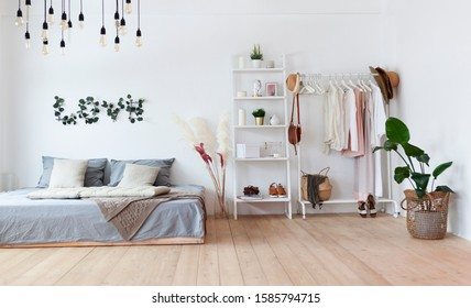 Scandinavian style, bedroom, bed, clothes rack in a modern light style. Female blouses and t-shirts on hanger on white background. Fashion blog, website, social media hero header template