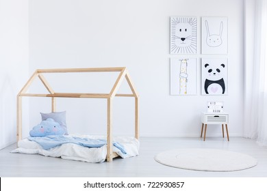 Scandinavian style boy's bedroom with blue pillow and coverlet on handmade bed and posters on wall