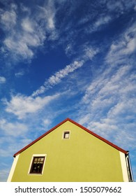 Scandinavian style house in yellow-green (chartreuse) color with gable roof against the background of bright blue sky and white clouds. Sample of European residential architecture.