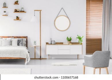 Scandinavian style white room interior with round mirror on the wall, wooden bed with pillows and blanket, cabinet and armchair. Real photo.