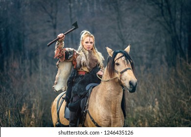 Scandinavian viking woman warrior riding horse holding ax above head looking threateningly. Northern warrior woman in forest with fur collar and war makeup.