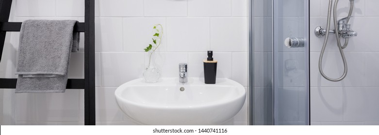 Scandinavian white bathroom with small basin and shower, panorama