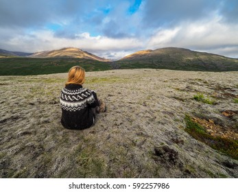 Scandinavian woman wearing traditionally patterned knitwear and lying on the mose, Iceland