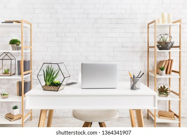 Scandinavian workplace. Laptop and florariums with succulent plants