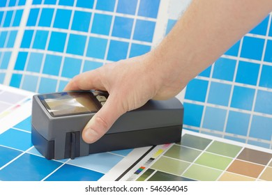 Scanning densitometer and a hand on a leaf of a cyan test print in a pre-press workshop