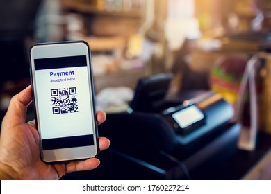 Scanning QR code payment with blurry cashier machine at counter service in coffee shop. Accepted generate digital pay without money. E wallet and cashless technology concept.