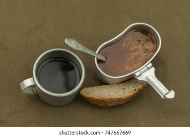 a scanty road meal: soup in a mess tin, cooled coffee in a vintage army mug, and a loaf of bread on a spread tarpaulin