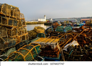 SCARBOROUGH, ENGLAND - APRIL 21: Commercial fishing equipment, boats and the lighthouse in Scarborough harbour. In Scarborough, England. On 21st April 2018.